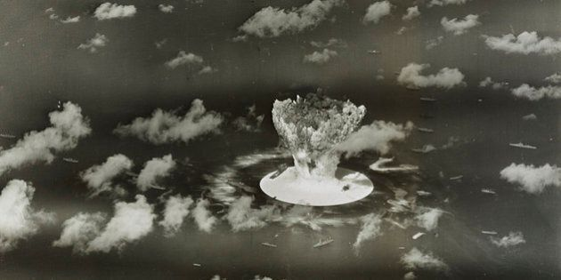 A mushroom cloud rises with ships below during Operation Crossroads nuclear weapons test on Bikini Atoll,...