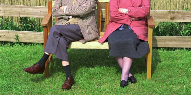 Elderly couple sitting on bench outdoors, low section