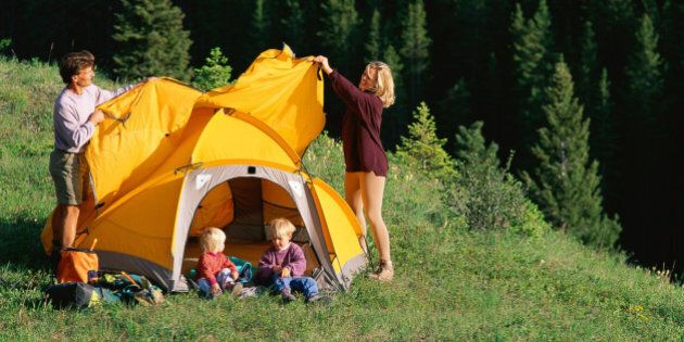 Mother and father pitching tent on