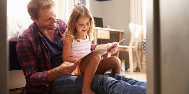 Father and young daughter reading together in bedroom
