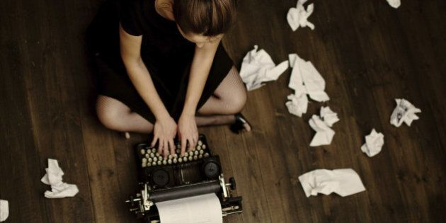 'Young woman sitting on the floor and typing, toned image, focus on the