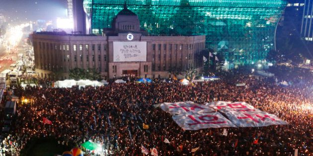 People hold a large banner, which reads,