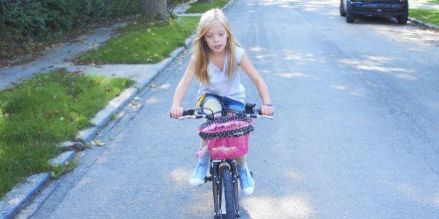 Girl riding her bike in the street
