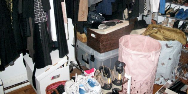 A cluttered closet full of clothes, shoes,accessories.