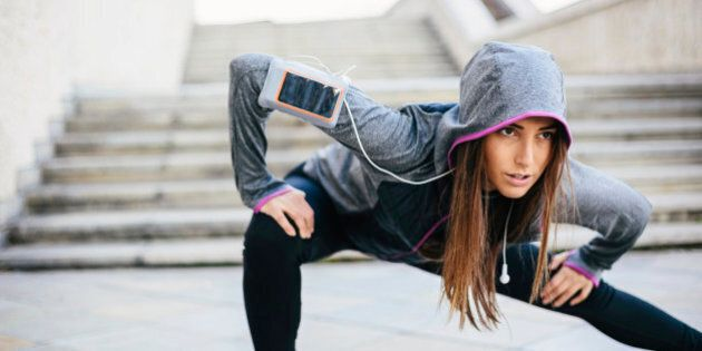 Young woman in sports wear exercising in the morning outdoors at urban scene, with copy space