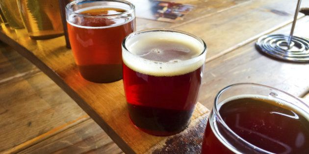 Craft beers are served together in a sampler tray for the beer enthusiast at a restaurant in