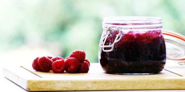 Delicious home-made raspberry jam in a jar and fresh raspberries on the