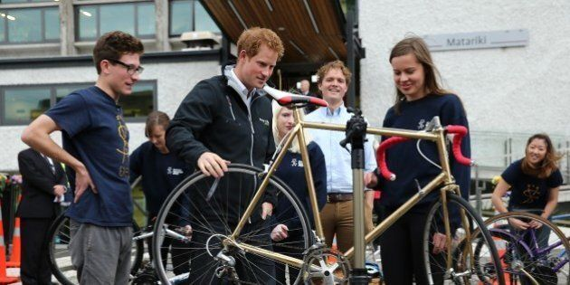 Britain's Prince Harry (2nd L) views bicycle repairs by members of the University of Canterbury's Student...