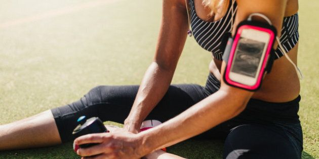Tired woman relaxing on sports field after hard fitness