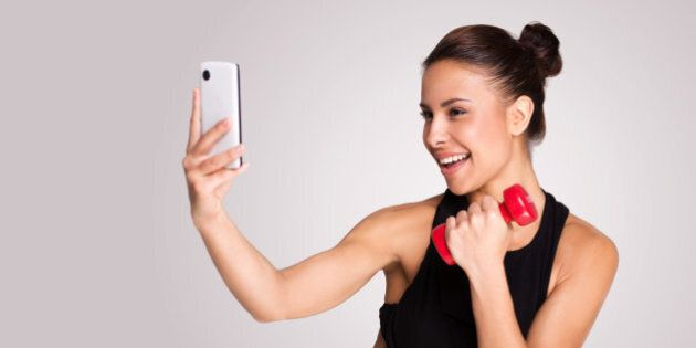 Young mixed race woman making selfie while taking fitness exercises, standing on grey