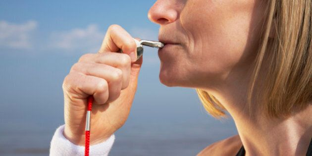 Woman blowing whistle on