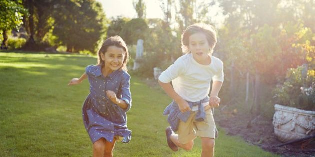 Two young children running in