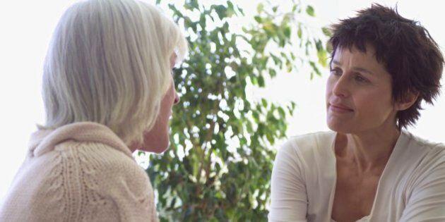 Middle-aged female couple talking on sofa