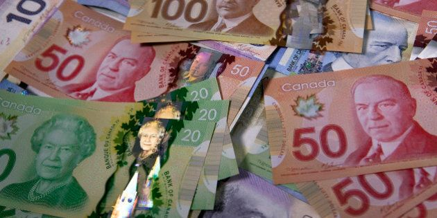 Canadian dollar bills are arranged for a photograph in Toronto, Ontario, Canada, on Tuesday, Feb. 26,...