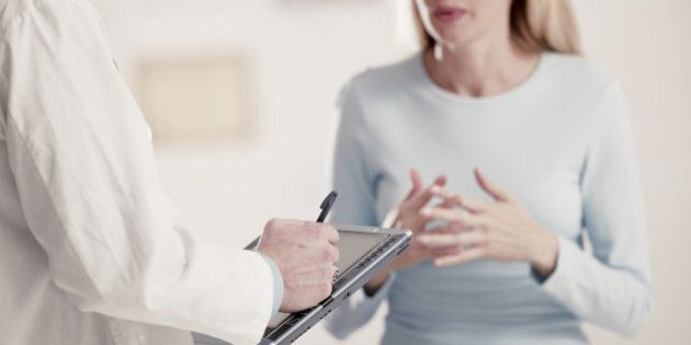 Doctor holding tablet PC talking to
