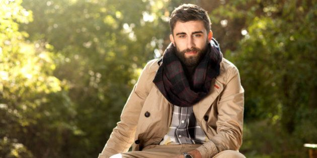 Fashion photo of young handsome man with suitcases in park. Autumn. Men wearing coat and scarf. Sunny