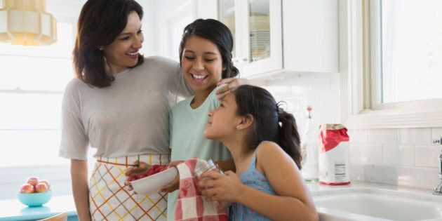 Mother and daughters hugging in kitchen