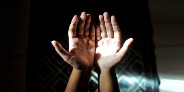 A muslim woman making dua(prayers) as light falls on her