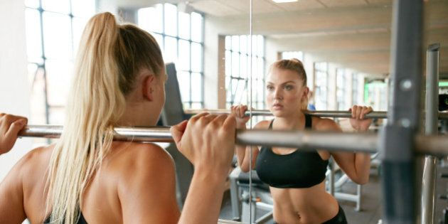 Muscular caucasian blond woman in a gym doing squats with a barbell on her shoulders while looking at...