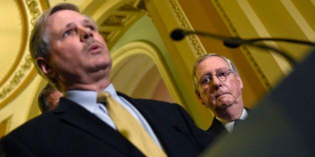 Senate Majority Leader Mitch McConnell of Ky. listens at right as Sen. John Hoeven, R.N.D. speaks during...