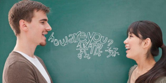 Portrait of smiling male teacher and student in front of chalkboard holding hands