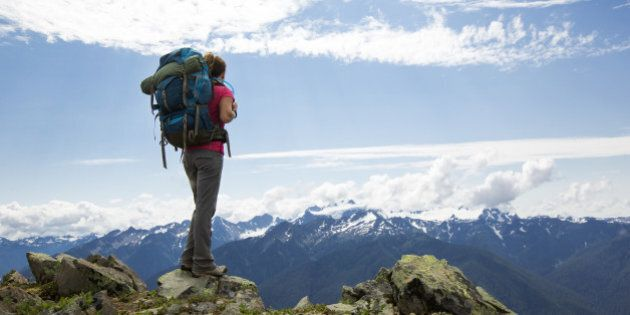 A female backpacking along a trail in the Olympic National Park.