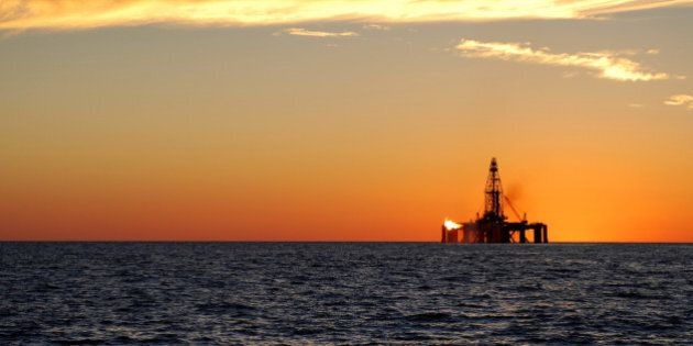 A wide angle view of an oil rig situated in the ocean exploring for oil and gas. The rig has a flame...
