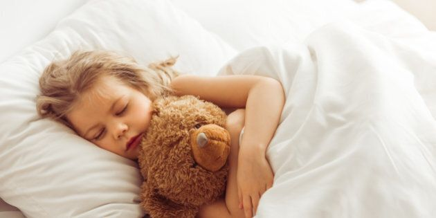Sweet little girl is hugging a teddy bear while sleeping in her bed at