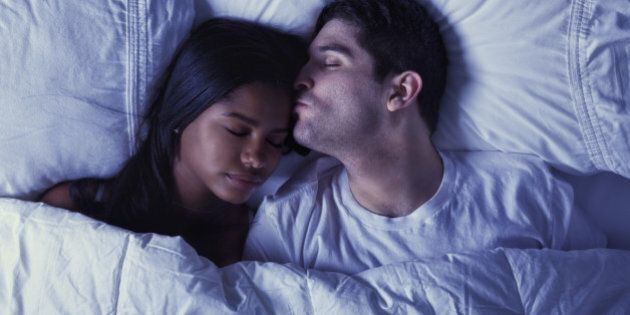 'Photo of an attractive young mixed-race couple lying on their bed, husband is kissing his wife goodnight...