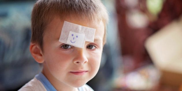 Close portrait of a boy with band aid on forehead, injured, sad but smiling