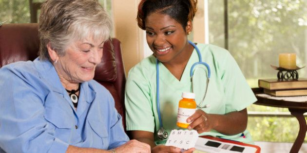 Caring, African descent home healthcare nurse conducts medical consultation with senior adult woman at...