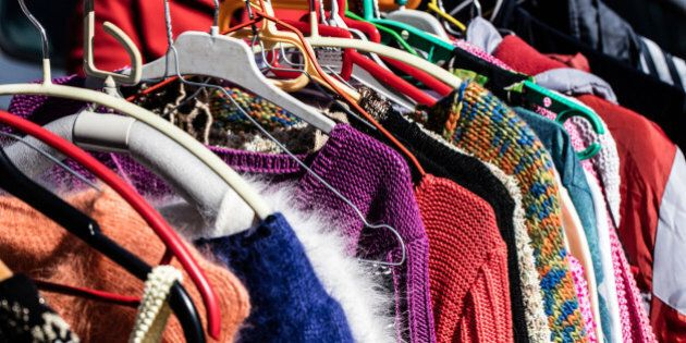 rack of fast fashion colorful women's sweaters on display for reselling,recycling,donation,reusing or...