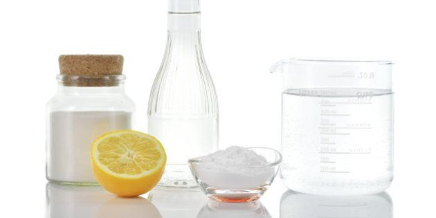 Eco-friendly natural cleaners. Vinegar, baking soda, salt, lemon and water in measuring cup on white...
