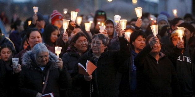 People take part in a march and candlelight vigil in the Attawapiskat First Nation in northern Ontario,...