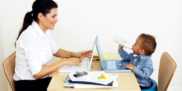 woman working from home sitting at table with little son