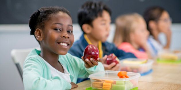 A multi-ethnic group of elementary age children are sitting at their desks and are eating their healthy
