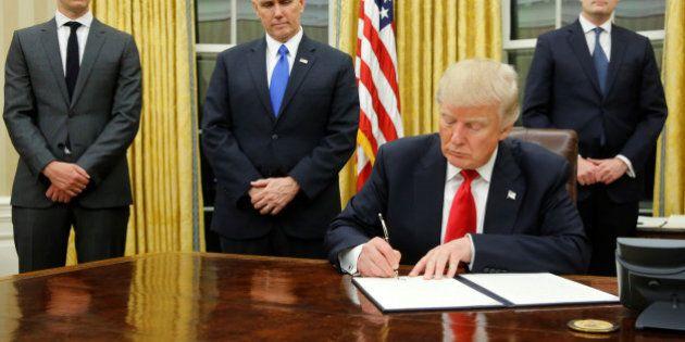 U.S. President Donald Trump, flanked by Senior Advisor Jared Kushner (standing, L-R), Vice President...
