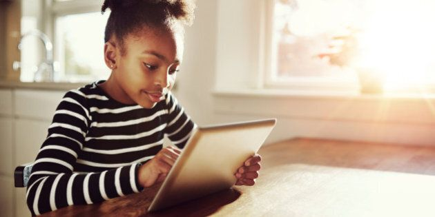 Young black girl with a fun afro hairstyle sitting at a table at home browsing the internet on a tablet...