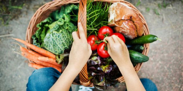 Hands of a girl putting freshly harvested vegetable in a basket