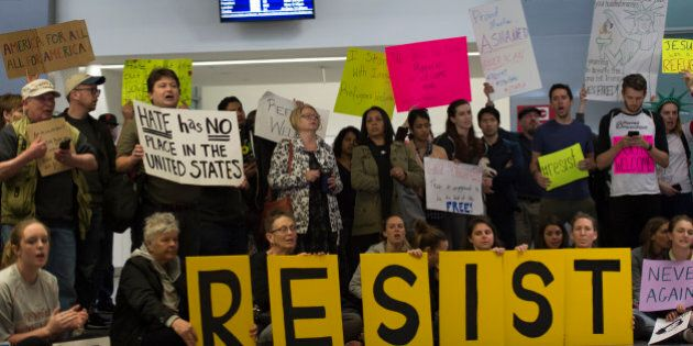 Protesters gather at the International Terminal Arrival Hall of San Francisco International Airport on...