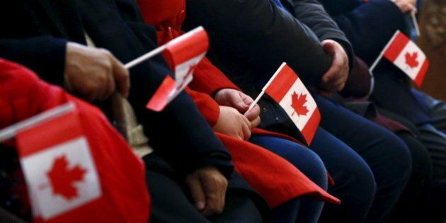 Syrian refugees hold Canadian flags as they take part in a welcome service at the St. Mary Armenian Apostolic Church at the Armenian Community Centre of Toronto in Toronto, December 11, 2015. REUTERS/Mark Blinch