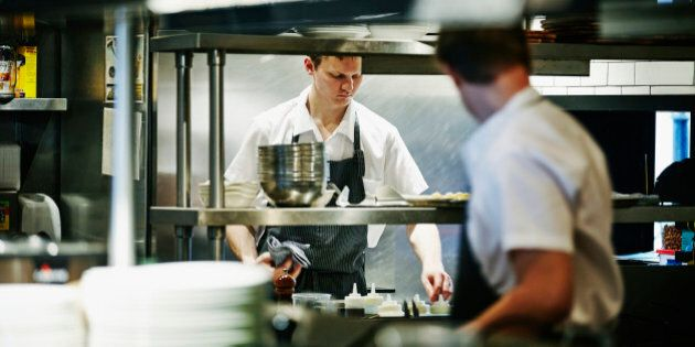Sous chef preparing ingredients at workstation in restaurant kitchen before dinner service