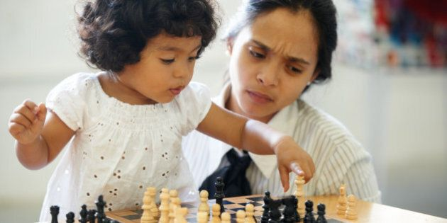 A cute little girl playing chess while her mom looks confused