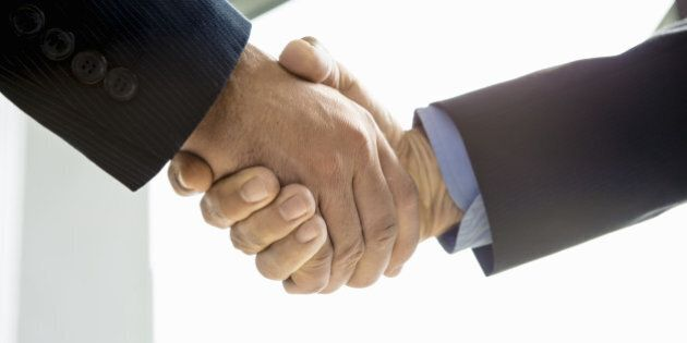 businesmen shaking hands in conference room