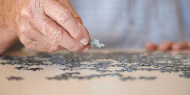 Elderly man, aged 77, looking for pieces of a jigsaw puzzle in a private retirement home