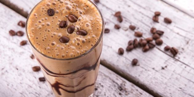 Cold chocolate milkshake frappe in tall glass with ice on white wood background