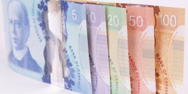 A closeup shot of Canadian currency on a white background with special attention to the reflection of...
