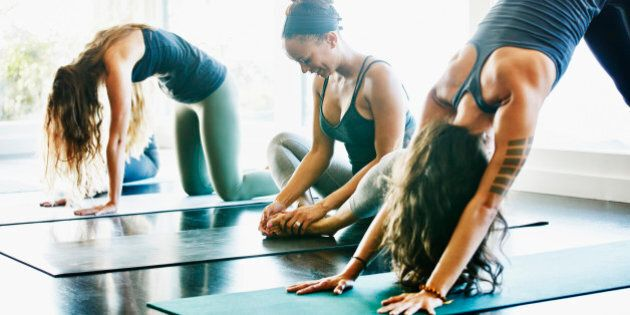 Group of women stretching before yoga class in studio