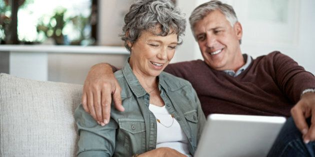 Shot of a mature couple using a digital tablet while relaxing on their sofa