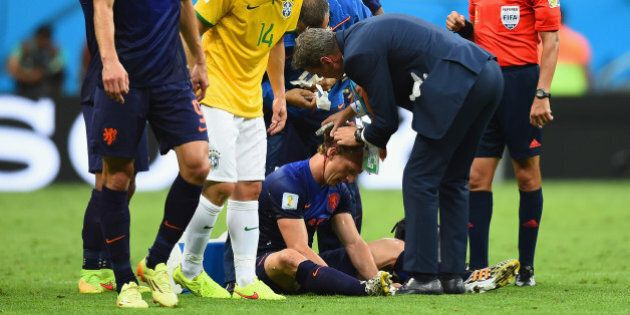 BRASILIA, DF - JULY 12: Dirk Kuyt of the Netherlands receives treatment after a clash as Maxwell of Brazil...